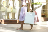 Detail of a young woman's body walking down a shopping street holding shopping bags. — Stock Photo