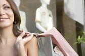 一名年轻女子的时尚商店,握着购物袋半脸. — 图库照片
