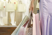 Detail close up of a woman's hand holding shopping bags by fashion store. — Stock Photo