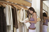 Young stylish woman looking at clothes in fashion store. — Stock Photo