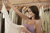 Mujer atractiva joven sosteniendo una prenda en una tienda de moda. — Foto de Stock