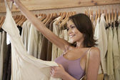 Young attractive woman holding a garment in a fashion store. — Stock Photo