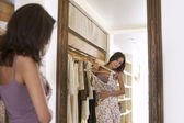 Young attractive woman trying on a dress in a fashion store, looking at her reflection in a mirror. — Stock Photo