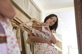 Cerca de una mujer atractiva joven probándose un vestido en una tienda de moda — Foto de Stock