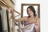 Joven mujer atractiva inspeccionando una prenda en una tienda de moda. — Foto de Stock