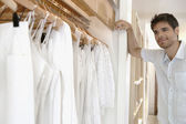 Young man looking at a selection of white clothes in a fashion store. — Stock Photo