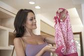 Mujer atractiva con una prenda en una tienda de moda. — Foto de Stock