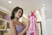 Tienda de mujer atractiva con una prenda de vestir de una manera, sonriendo. — Foto de Stock