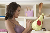 Close up view of a young woman looking at a handbag's design in a store. — Stock Photo