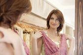 Cerca de una joven que trata de una prenda nueva en una tienda de moda. — Foto de Stock