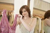 Cerca de una joven mujer mostrando una prenda nueva en una tienda de moda. — Foto de Stock