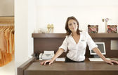 Business owner leaning on her fashion store's desk, feeling proud. — Stock Photo