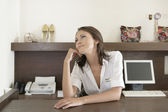 Young businesswoman day dreaming whilst sitting by store's payment desk. — Stockfoto