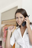 Young attendant using the telephone in a fashion store. — Stock Photo