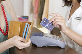 Close up detail of a store attendant holding a credit card near a card reader. — Foto de Stock