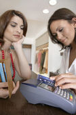 Close-up detail van een winkel begeleider vegen een credit card in een kaartlezer. — Stockfoto