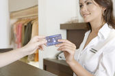 Close up detail of client's hand handing over credit card to a smiling store attendant. — Stock Photo