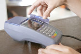 Close up of a store attendant's hand sweeping a credit card in a card reader. — Stock Photo