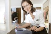 Lagra skötare ringer upp en kortläsare detaljerna i ett kreditkort i en modebutik. — Stockfoto