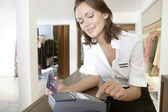 Shop assistant dialing into a card reader the details of a credit card in a fashion store. — Stock Photo
