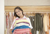 Shop assistant holding a pile of clothes in a fashion store — Stock Photo