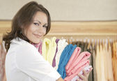 Close up portrait of young store attendant holding a pile of clothes in a fashion store. — Stock Photo