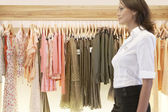 Blured figure of a sophisticated store assistant walking through a fashion store. — Stock Photo