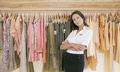 年轻的店助理常设自豪地由一线时装商店里的衣服. — 图库照片