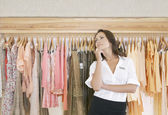 Young store attendant standing thoughtfuly by a line of clothes in a fashion store. — Stock Photo