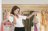 Young store attendant holding hangers with clothes in a fashion store. — Stock Photo