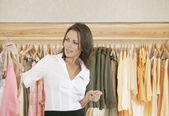 Young store attendant looking at hangers with clothes in a fashion store. — Stock Photo