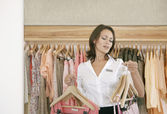 Young store attendant ordering hangers with clothes in a fashion store. — Stock Photo