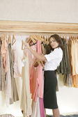Female store attendant arranging a line of clothes in a fashion store. — Stock Photo