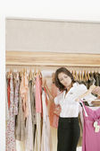 Store attendant holding a pile of clothes in a fashion shop. — Stock Photo