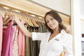 Gülümseyen, mağazanın raylar üzerinde giysi sıralama bir mağaza asistanı yukariya. — Stok fotoğraf
