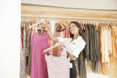 Store assistant sorting clothes on store's rails, smiling. — Stock Photo