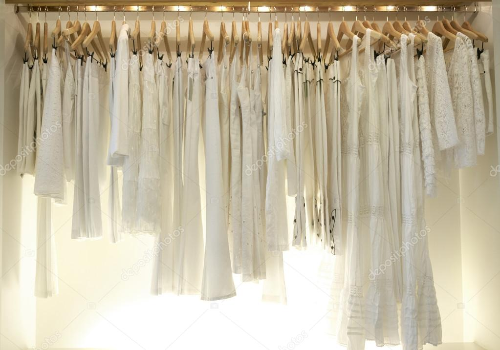 clothes hanging on wooden hangers in a fashion store. - Stock Image