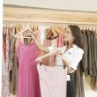 Store assistant sorting clothes on store's rails, smiling. — 图库照片