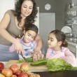 Young mum chopping vegetables with twin daughters in a family home kitchen. — Photo