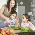 mladá maminka sekání zeleniny s dvěma dcerami v rodinné domácí kuchyně — Stock fotografie
