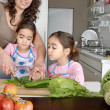 Mum and twin daughters learning to chop vegetables together in the kitchen, using a chopping board and surrounded by fruit and vegetables. - Stock Photo