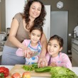 Young family kids learning to chop vegetables in the kitchen with mum, smiling. - Stock Photo