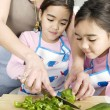 Mum chopping vegetables with twin daughters in a family home kitchen. — Stock Photo