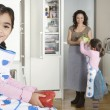 Young mum taking vegetables out of the fridge in a home kitchen with twin daughters. — Stock Photo