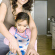 Young mum chopping vegetables with young daughter in a family home kitchen. — Stock Photo
