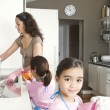 Young mum and daughter washing up and drying dishes in a home kitchen. — Stock Photo