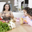 Stock Photo: Mum and twin daughters peeling poratoes at a kitchen's table.