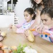 Young mum teaching twin daughters how to peel potatoes. - Stok fotoğraf