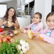 Mother and twin daughters learning to peel potatoes together in the kitchen, using a chopping board with fruit and vegetables. — Stock Photo