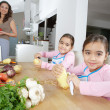 Mother and twin daughters learning to peel potatoes in the kitchen, using a chopping board with fruit and vegetables. — Stock Photo
